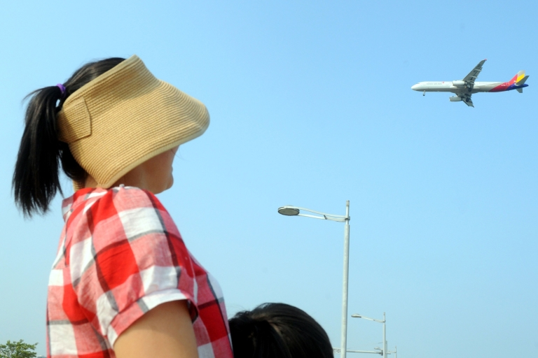 <p>A South Korean woman looks at a Asiana Airlines plane as it lands at Incheon International Airport in Incheon, west of Seoul on June 18, 2011. South Korean troops have fired at a passenger jet flying from China with 119 people on board after mistaking it for a North Korean aircraft, amid increasingly fraught relations on the divided peninsula.</p>