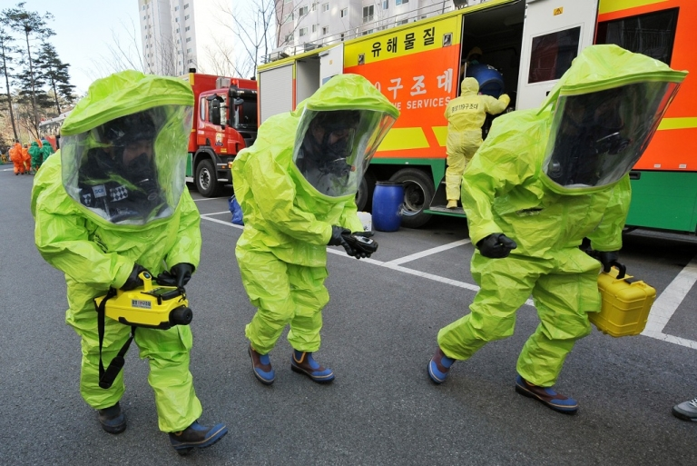 <p>South Korean rescue team members participate in a civil defence drill against a chemical warfare in Paju near the DMZ separating the two Koreas, in December  2010. South Korea launched its biggest-ever civil defence drill amid tensions over North Korea's deadly artillery attack in November and its nuclear programmes. New satellite images raise questions about Kim Jong-il's expansion of that program.</p>