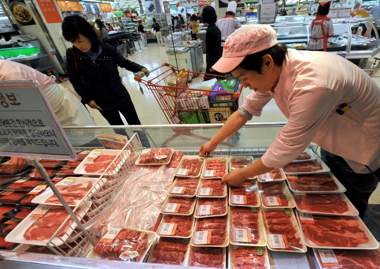 <p>A South Korean employee displays Australian beef at Lotte Mart, which suspended all sales of all US beef in South Korea after a case of mad cow disease was discovered in central California.</p>