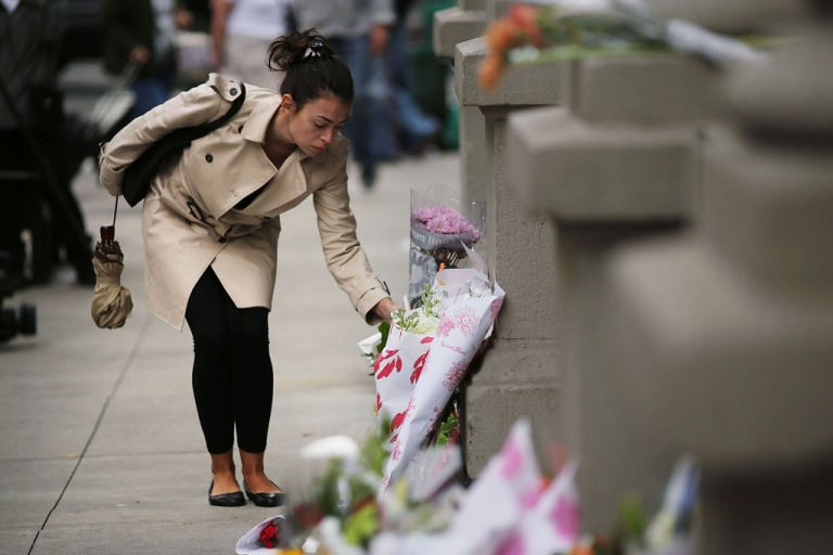 <p>A woman leaves flowers at the building where two Krim children were stabbed to death on October 25, 2012, in New York City. Their nanny, 50-year-old Yoselyn Ortega, pleaded not guilty to murder charges on November 28, 2012.</p>