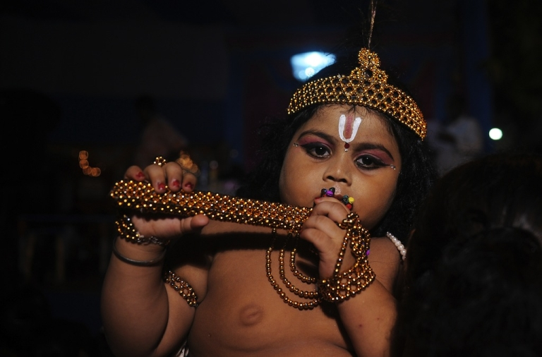 <p>A young Indian Hindu devotee dressed as the Hindu God Lord Krishna stands amidst his family members before a fancy dress competition held at a local temple in Kolkata on August 9, 2012 on the eve of 'Krishna Janmashtami'. The Janmashtami falls on August 10 this year, marking the birth of the Hindu God Lord Krishna.</p>