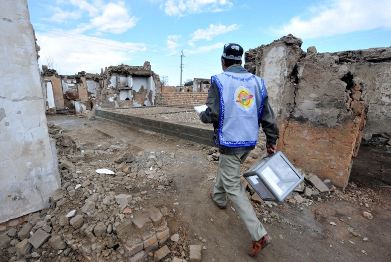 <p>A member of the local electoral committee walks with a ballot box through the destroyed homes of ethnic Uzbeks in Osh, Kyrgyzstan on Oct. 10, 2010.</p>