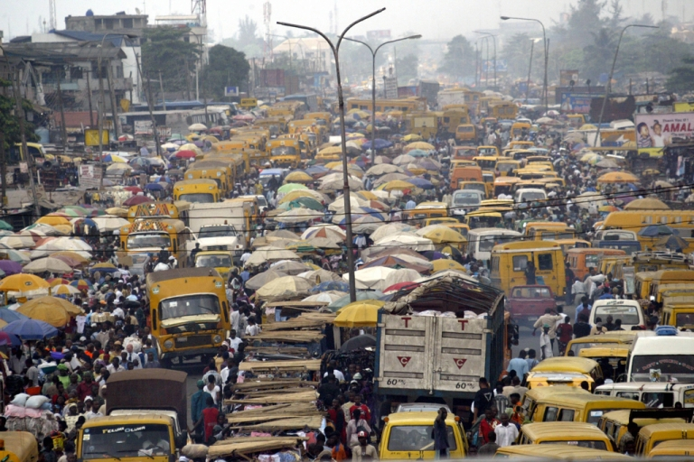 <p>People walk struggling for space between public transport buses and trucks at the burstling Lagos bus stop.</p>