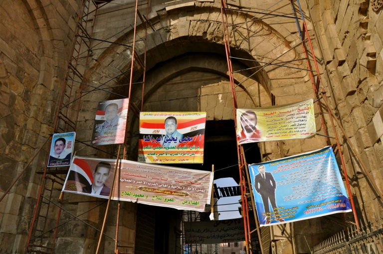 <p>Advertisements for parliamentary candidates hang from scaffolding in Cairo in October 2011.</p>