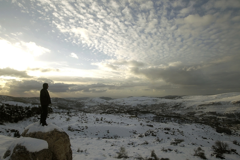 <p>A Lebanese forest ranger observes the sunset from the cedar trees reserve of Baruk in the Shouf mountains, southeast of Beirut, following a snow storm and cold wave which hit the east Mediteranean country after several months of drought.</p>