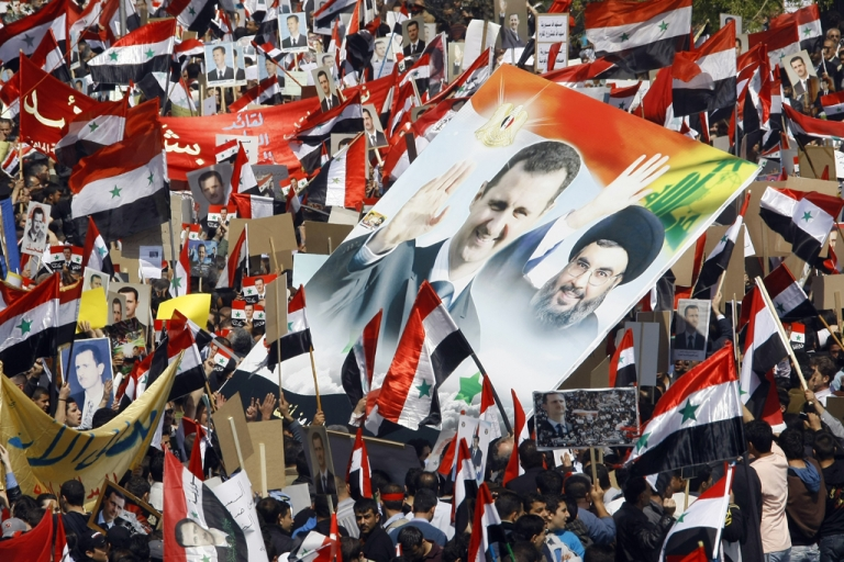 <p>Syrians hold portraits of President Bashar al-Assad (Left) and Lebanon's Hezbollah chief Hassan Nasrallah (Right) during a rally. Hezbollah is losing support due to its unwavering support for the Syrian regime and the political fall-out of the Syrian uprising is deepening the political divides in Lebanon.</p>