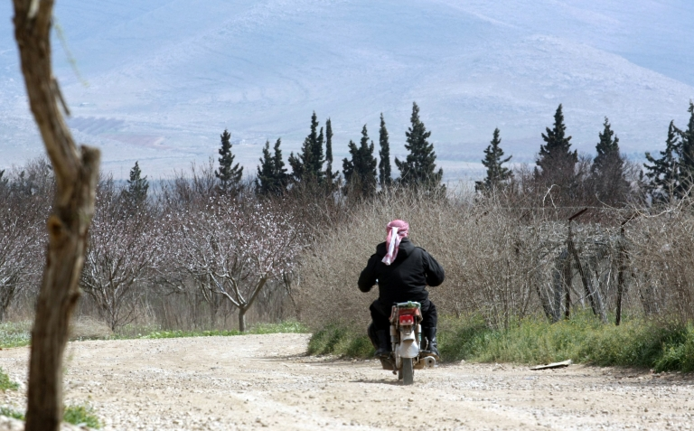 <p>A Lebanese man rides his motorbike on March 28 in the area of Joura, only a few meters from the place where the Syrian government forces clashed with Syrian rebel troops near the al-Qaa area of the Bekaa valley on the Syrian-Lebanese border.</p>