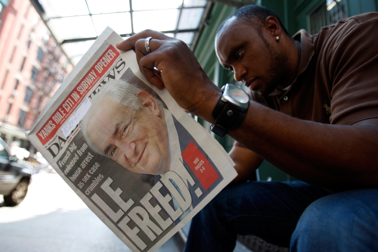 <p>A man reads a paper with Dominique Strauss-Kahn on the front cover as media gather outside of the apartment where former IMF chief Dominique Strauss-Kahn is staying in New York.</p>