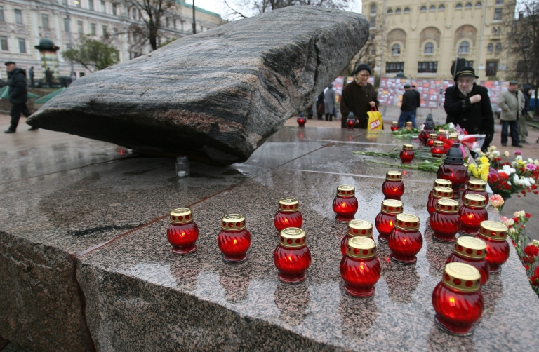 <p>People place candles near the Solovetsky stone in front of the FSB, formerly KGB, headquarters in Moscow on October 29, 2009.</p>