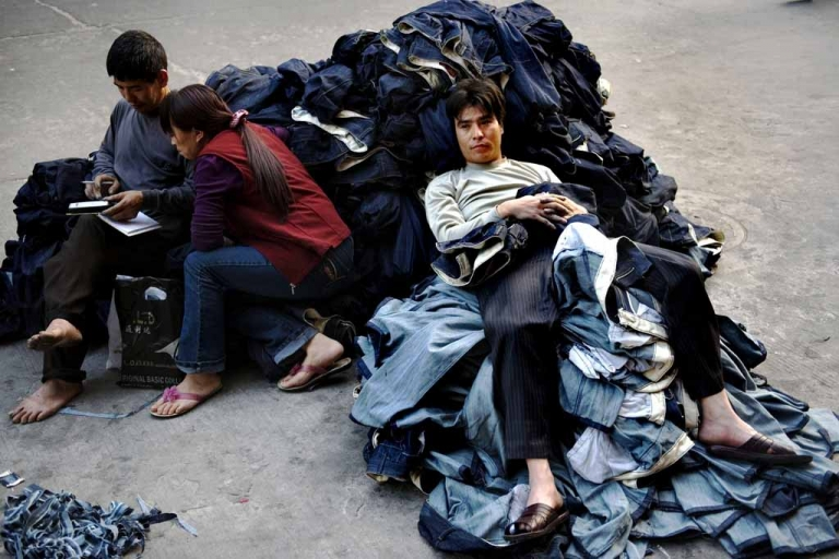 <p>A worker sits on a pile of jeans in a garment factory in Guangzhou, China.</p>