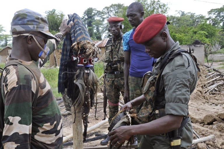 <p>Seven UN peacekeepers were killed in an ambush near Ivory Coast's border with Liberia. Here Ivory Coast militia look at masks in a burned-out village at Liberia's border with Ivory Coast on April 21, 2011.</p>
