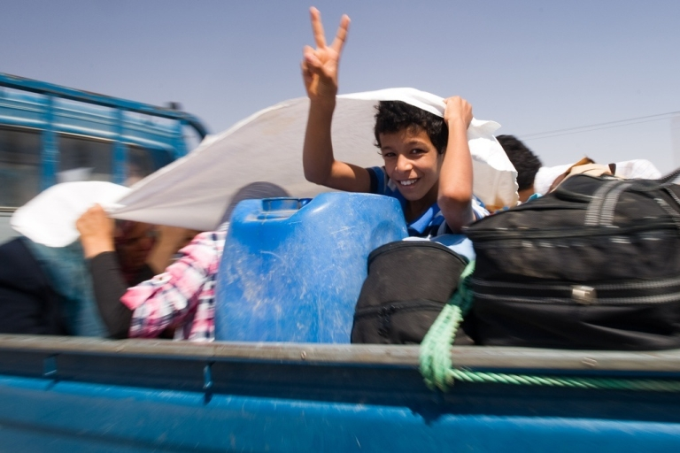 <p>A Libyan boy fleeing with his family flashes the V-sign for victory on the road out of Bani Walid on September 12, 2011. Civilians poured out of the Libyan oasis town fearful of new fighting between Muammar Gaddafi's forces and the rebel troops that have besieged the Bani Walid valley</p>