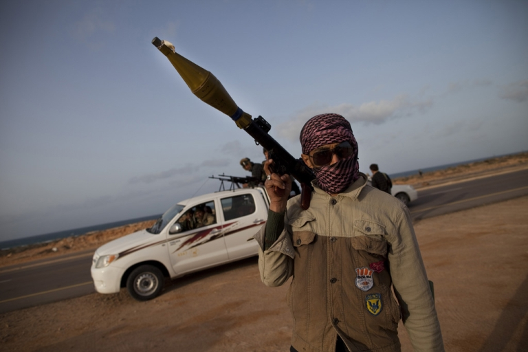 <p>A fighter carries an RPG launcher on the road outside of Brega.</p>