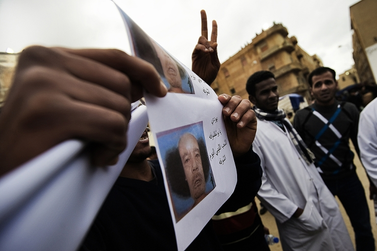 <p>A Libyan holds pictures depicting a balding Libyan leader Moamer Kadhafi after the Muslim Friday prayers outside the courthouse in the eastern city of Benghazi on February 25, 2011.</p>