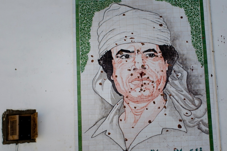 <p>A bullet-ridden mosaic of Gaddafi is seen on the wall of a building in August 2011 in Tripoli, Libya. Gaddafi amassed billions. What will happen to them now that he's gone?</p>