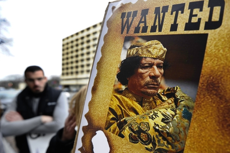<p>Libyan nationals protest against Muammar Gaddafi's regime in front of a building housing Libyan embassy in Washington, DC, on February 24, 2011. The Internation Criminal Court chief prosecutor said that Gaddafi should be investigated for crimes against humanity.</p>