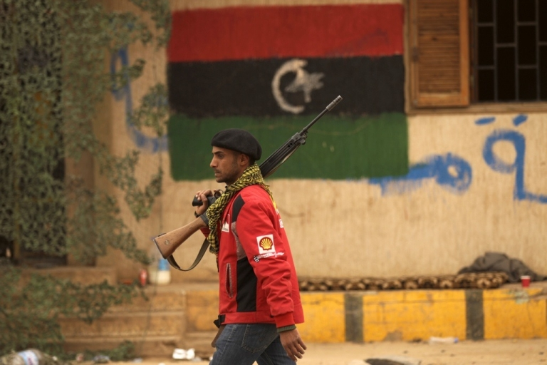 <p>A Libyan rebel walks past a military position decorated with the rebellion flag at the southern entrance of the coastal city of Benghazi on March 15, 2011, as Libyan government forces assaulting the key city of Ajdabiya outflanked insurgents and cut off the road north to Benghazi, rebel sources said amid scenes of chaos in the town.</p>