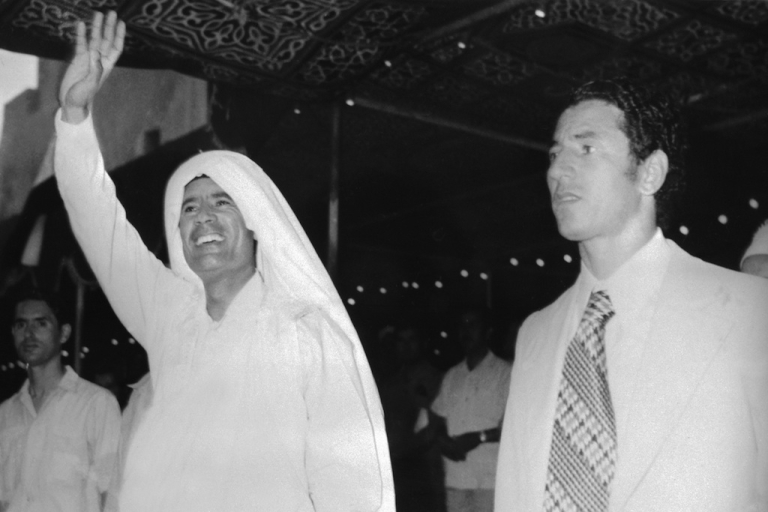 <p>Modest beginnings in 1975, Gaddafi wears a simple white head scarf whilst waving to a crowd in Tripoli. All photos from AFP/Getty.</p>