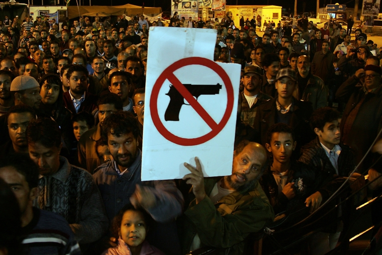 <p>A Libyan demonstrator holds a sign as people gather for a protest calling for the disarming of militiamen in the eastern city of Benghazi on Dec. 13, 2011.</p>