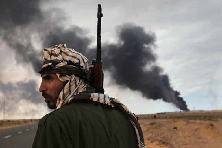 <p>A Libyan rebel scans the horizon as an oil facility burns on March 9, 2011 near Ras Lanuf, Libya. The rebels pushed back government troops loyal to Libyan leader Muammar Gaddafi towards Ben Jawat.</p>