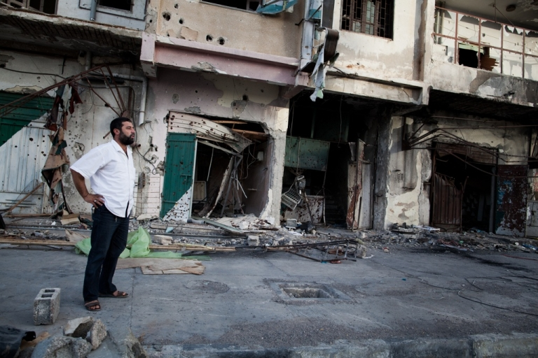 <p>A local resident stands in front of his war-torn apartment building in Misrata, Libya on Sept. 3, 2011.</p>