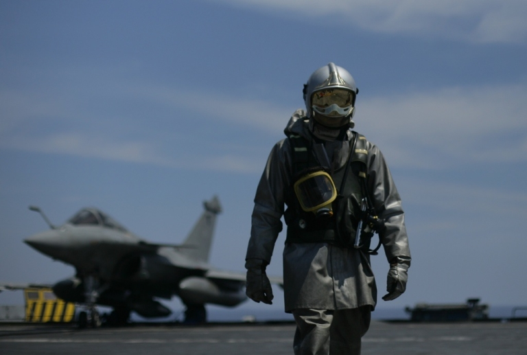 <p>A French Navy firefighter looks on as he walks past a Rafale jet fighter on the flight deck of the Charles de Gaulle aircraft carrier on April 21, 2011 during NATO operations off the coast of Libya.</p>