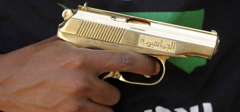 <p>A man holds a golden gun that he says he found in the former compound of ousted leader Muammar Gaddafi. More than 20,000 criminal prisoners escaped during the revolution. And now police say they are all armed.</p>