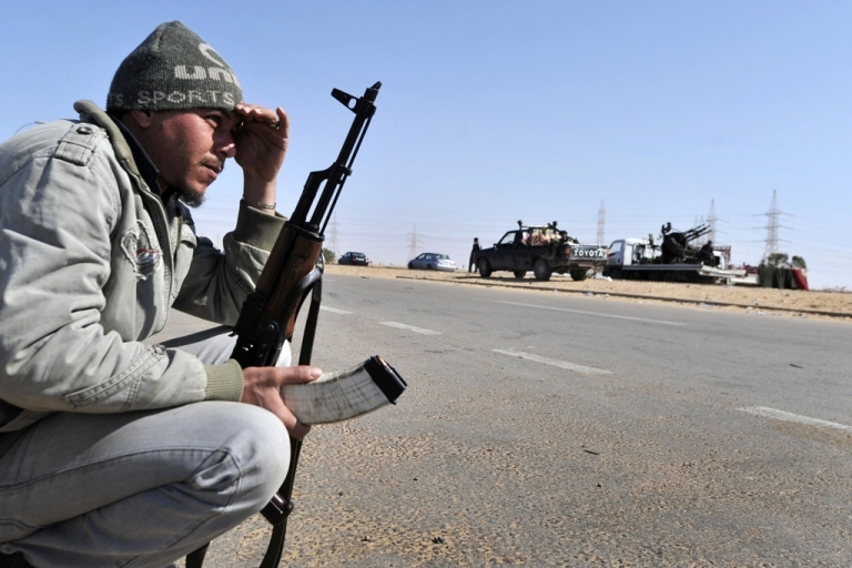 <p>A Libyan rebel crouches at the last check point before the key city of Ajdabiya on March 23, 2011. Government forces have encircled the town.</p>