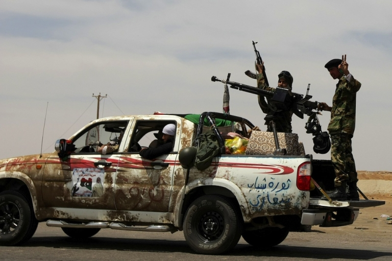 <p>Libyan rebels drive to the battle front line between the strategic town of Ajdabiya and the town of Brega, on April 21, 2011.</p>