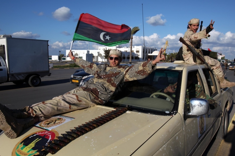 <p>Libya's former rebels, who have now joined the new Libyan army, wave Libya's new flag as they parade through Tripoli on Feb. 14, 2012.</p>