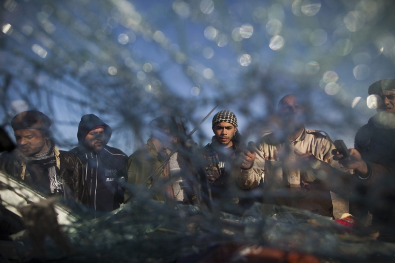 <p>A group of rebel fighters gather near the car of a man who was killed when a air strike hit his car on March 8, 2011.</p>
