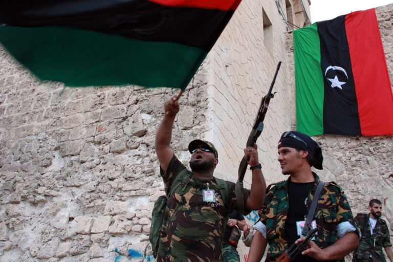 <p>Libyan rebels from the National Transitional Council wave the newly adopted Libyan flag in Martyr's Square in the capital Tripoli during a rally on the third on September 2, 2011.</p>