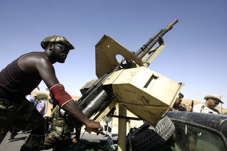 <p>Libyan rebel forces said they advanced Thursday on the cities of Sirte and Bani Walid, two of the last strongholds of deposed leader Muammar Gaddafi. Here a Libyan rebel fighter handles a machine gun fixed on the top of a truck at the frontline with the city of Bani Walid on September 11, 2011.</p>
