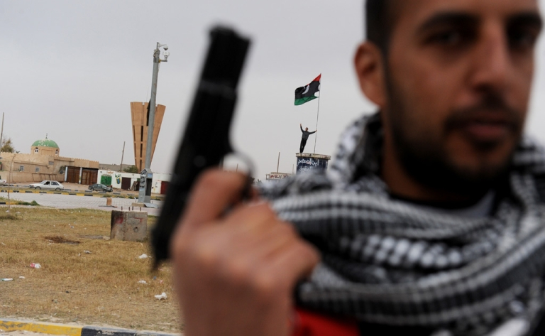 <p>A rebel fighter stands with his handgun at a roundabout in the center of town in the eastern Libyan city of Ajdabiya on March 15, 2011.</p>