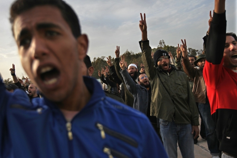 <p>Rebel volunteers cheer on their first day of military training at a rebel militia center on March 1, 2011, in Benghazi, Libya.</p>