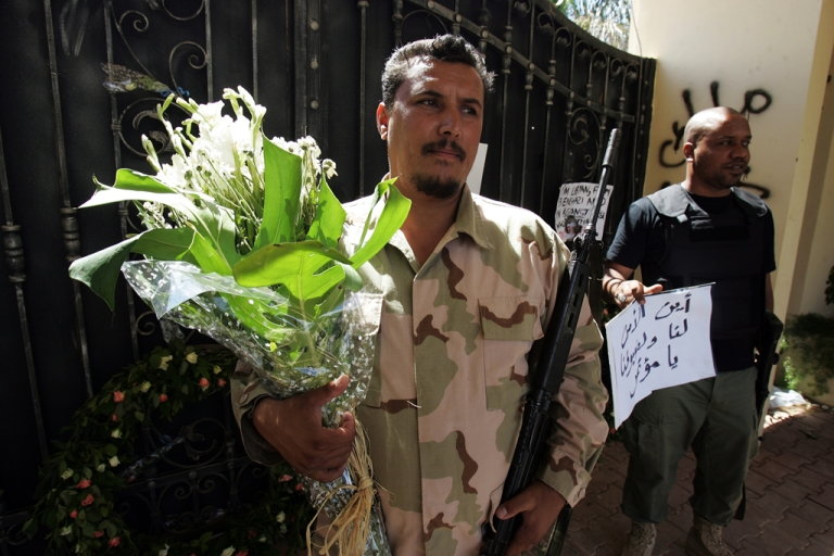 <p>Libyan security guards hold flowers and slogans left by people protesting against last week's attack, in which ambassador Chris Stevens died, at the main entrance of the US consulate in Benghazi. Around 30,000 Libyans joined a rally in Benghazi on September 21, 2012, protesting the powerful militias that have run rampant in the country.</p>