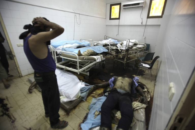 <p>A man looks at the dead bodies in the morgue at he general hospital in the restive Abu Salim neighborhood of Tripoli, on August 26, 2011. The putrefying bodies of around 80 people were found in the hospital, apparently the unlucky victims of fighting that prevented the wounded from being treated, an AFP correspondent reported.</p>
