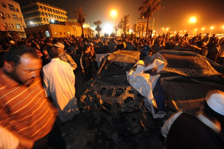 <p>People gather around the remains of car which exploded near the headquarters of Libya's rebels in their eastern bastion of Benghazi late on May 3, 2011.</p>