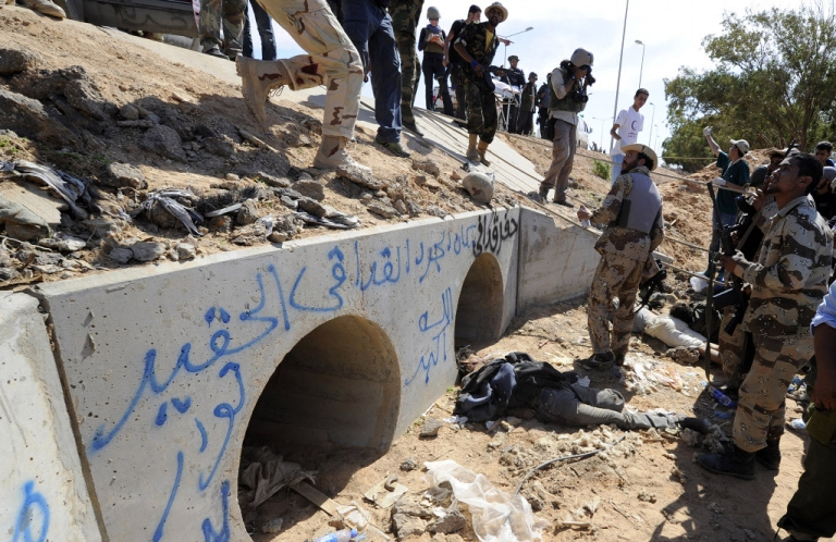 <p>Libyan National Transitional Council (NTC) fighters stand outside drainage pipes where ousted Libyan leader Muammar Gaddafi was captured, as the body of a loyalist lies on the ground, in the coastal Libyan city of Sirte on October 20, 2011.</p>