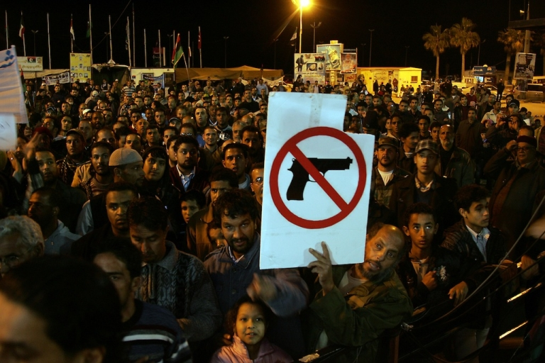 <p>A Libyan demonstrator holds a sign as people gather for a protest calling for uniting the army and disarming militiamen in the eastern city of Benghazi on December 13, 2011. AFP PHOTO/ABDULLAH DOMA</p>