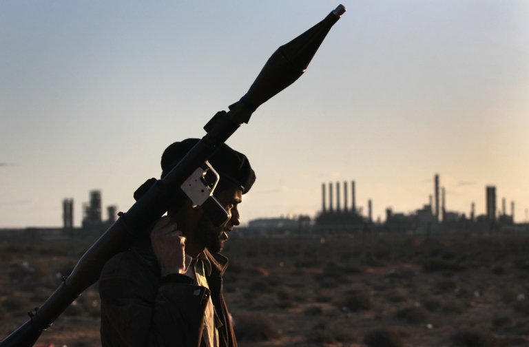 <p>A Libyan rebel carries a rocket propelled grenade near strategic petroleum facilities on March 6, 2011 in Ras Lanuf, Libya.</p>