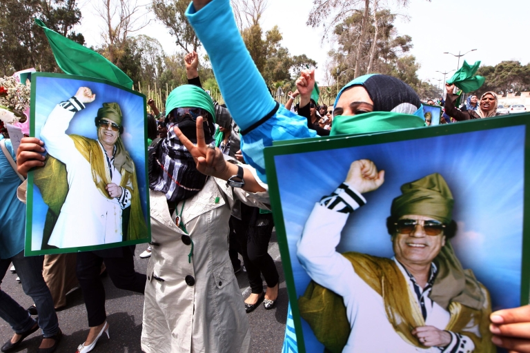 <p>Libyan women hold pictures of Libyan leader Muammar Gaddafi as they rally outside the Rixos Hotel where foreign journalists are based in the Libyan capital Tripoli on May 22, 2011 in Tripoli.</p>