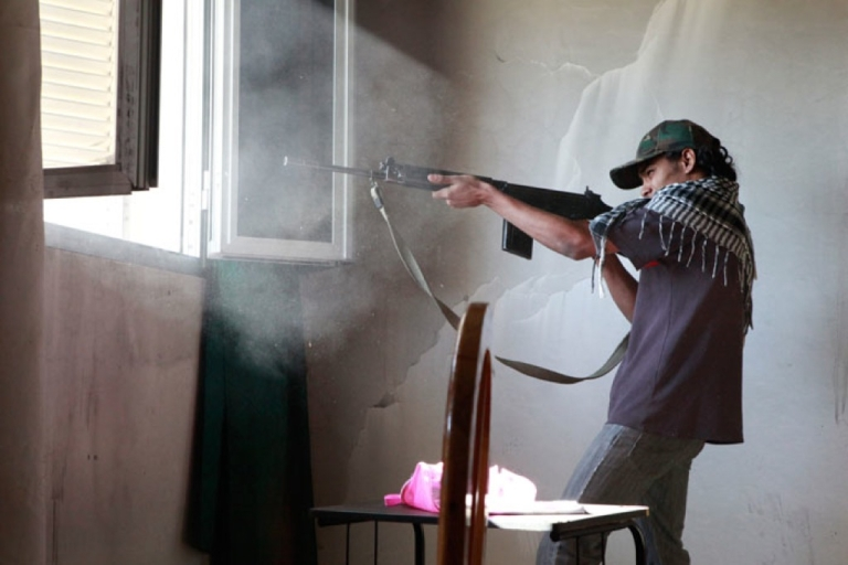 <p>Mohammed Al Derbale, 19, fires an FN rifle at Gaddafi troops from the window of an abandoned farmhouse in Dafnia.</p>