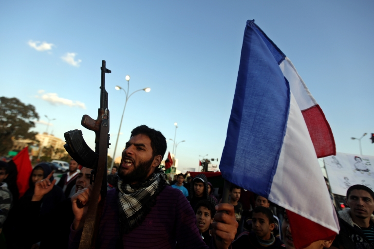 <p>A Libyan rebel waves the French flag during a march in Benghazi to support the international coalition on March 24, 2011, as rebels battled on to the eastern oil town of Ajdabiya today as plans firmed for NATO to take over coalition operations after Tripoli came under attack for a sixth day and death tolls mounted.</p>