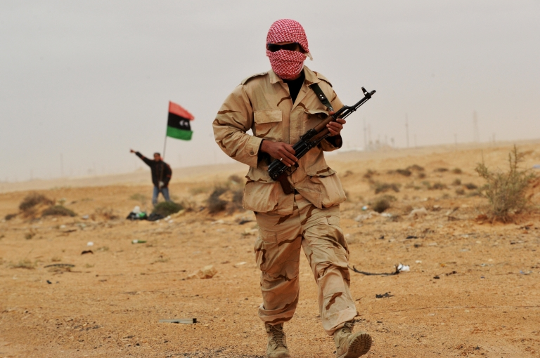 <p>A rebel fighter walks toward clashes between pro-Gaddafi forces and rebels on the outskirts of the north-central Libyan town of Bin Jawad on March 8, 2011.</p>