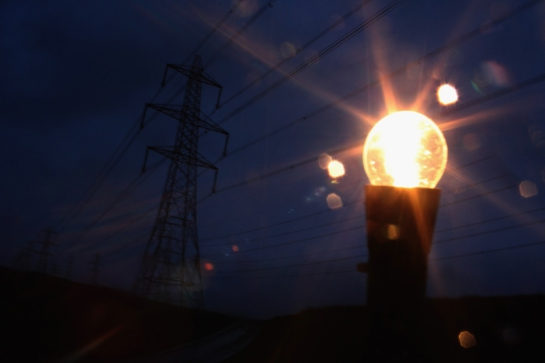 <p>An incandescent light bulb is illuminated next to electricity pylons.</p>