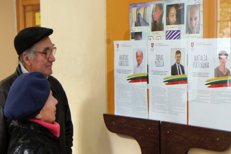 <p>Voters read about the candidates for the parliamentary elections at a polling station in Vilnius, Lithuania, on Oct. 14, 2012.</p>