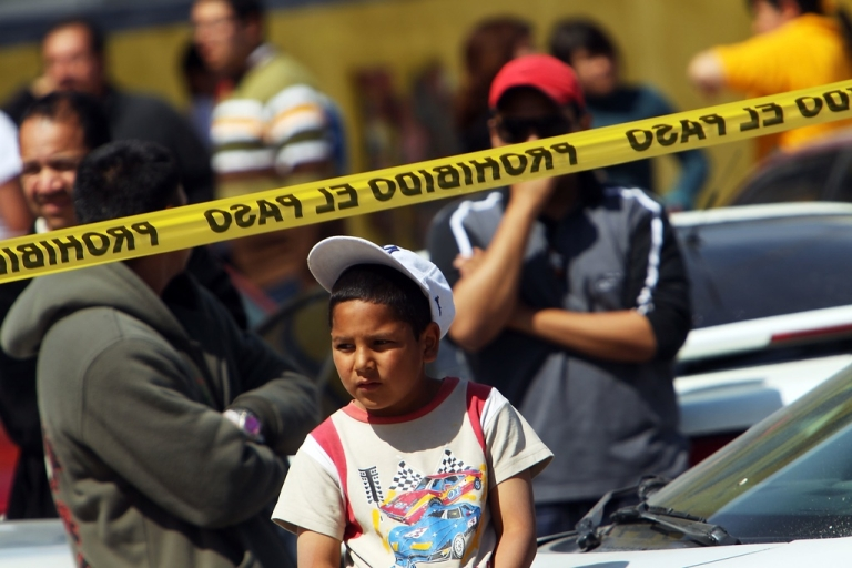 <p>In Texas, children as young as 11 have been pulled into the trade. Here, a little boy looks over a crime scene in the Mexican border town of Ciudad Juarez.</p>