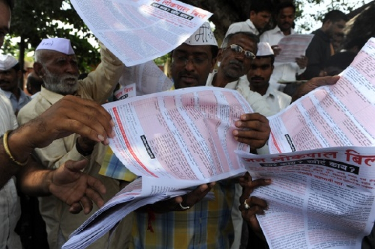 <p>Supporters of hunger-striking activist Anna Hazare grab pamphlets explaining the anti corruption bill