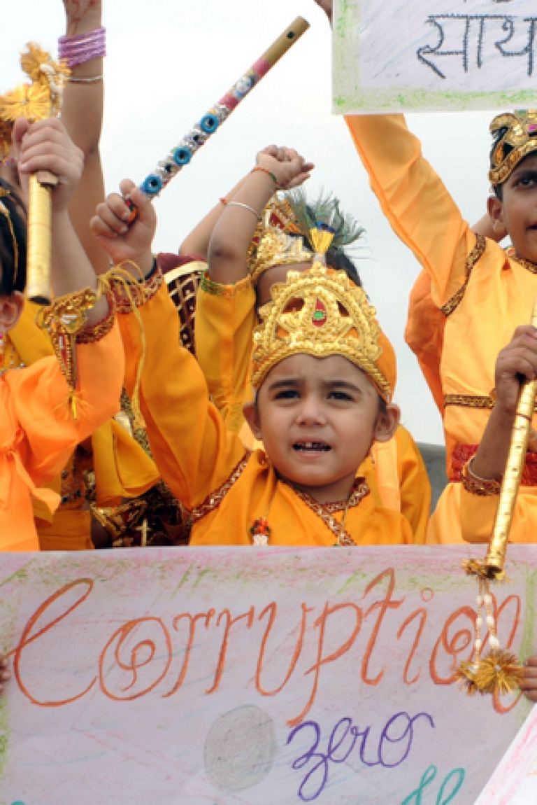 <p>Indian children dressed as Hindu god Krishna hold placards as they shout slogans against corruption during a demonstration in Amritsar on August 20, 2011. The threat of amendments forced the government to put a proposed bill to create a powerful ombudsman to fight corruption on hold late Thursday. The parliament will not reconvene until February.</p>
